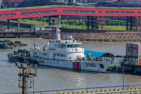 SHANGHAI, CHINA - Oct 08, 2017: Chinese Coast Guard (CCG) offshore patrol vessel No. 31102 berthed at the pier next to China's Biggest coal-fired power plant in Shanghai. 報道画像