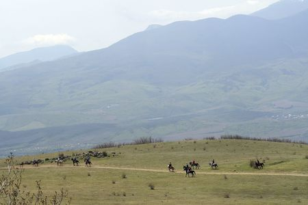 The group of horsemen going from mountains photo