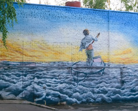 Picture on a brick wall, depicting a boy standing with a paddle boat, floating on the waves to the solar horizon Редакционное