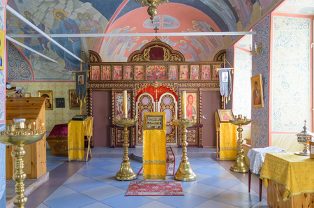 iconostasis: BOLHOV OF OREL REGION, RUSSIA - AUGUST 15, 2015: Several lectern and candlesticks in hall of worship in Holy Trinity Church. Iconostasis in background Editorial