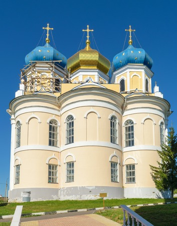 is cloudless: Church with three blue and golden domes against blue cloudless sky on sunny summer day.