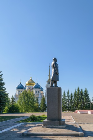 ulyanov: BOLHOV OF OREL REGION, RUSSIA - AUGUST 15, 2015: Monument to Lenin on a background of the Holy Trinity church. Side view, in profile. Sunny clear summer day. Cloudless blue sky