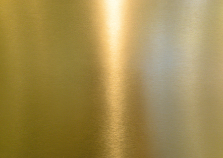 Detail of shiny polished metal surface golden (yellow) color with highlights Stock Photo