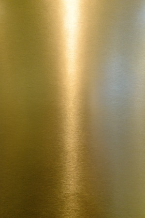 coloured background: Detail of shiny polished metal surface golden (yellow) color with highlights Stock Photo