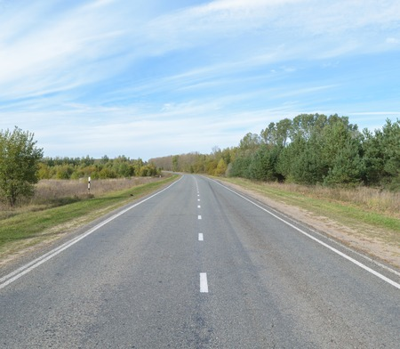 intermittent: Receding into the distance suburban asphalt highway with white intermittent markings. Stock Photo