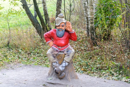 woodland sculpture: Orel, Russia - October 18, 2015: Sculpture of an old man sitting on a stump in a forest in the national park Orlovskoye Polesie