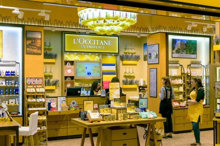 afimall: Moscow, Russia - March 29, 2016: Saleswoman in a corporate yellow interior of boutique LOccitane in the mall AFIMALL for the sale of organic cosmetics from Provence (France) Editorial