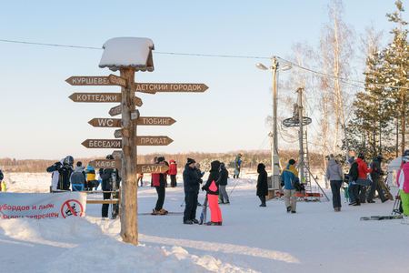 gorki: Orel, Russia - January 10, 2016: People in ski equipment near a wooden post with direction signs in the ski park Gorki
