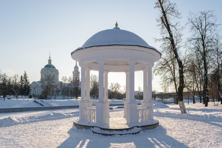 White arbor with the columns, standing on the shore of frozen river  in winter.