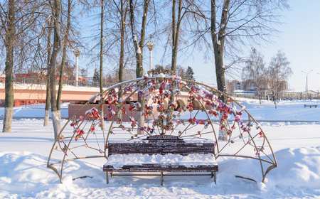 desires: Orel, Russia - January 24, 2016: Decorated from padlocks Bench of desires on the background of the Alexander bridge across the river Orlik in the center of city in winter