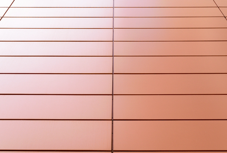 facade: Surface of the wall of the building, covered with pink metallic rectangular panels.