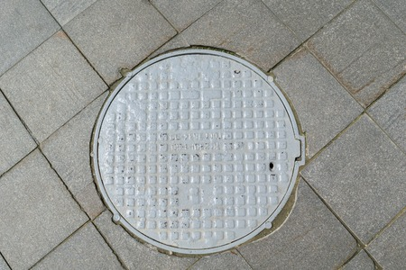 holed: Grey metal cover of the hatch covering the technology pit to underground utilities. Stock Photo