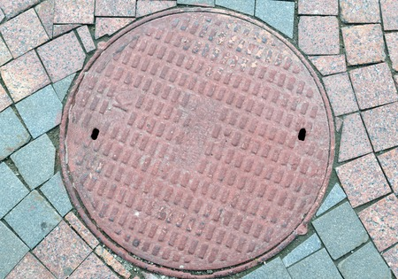 holed: Textured metal manhole cover with holes, closing the technological wells for underground communications.