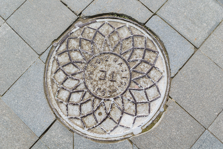 holed: Metal manhole cover with ornaments covering the technology pit to underground utilities.