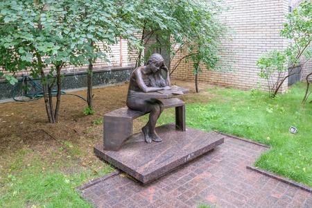 linguistic: Moscow, Russia - July 07, 2016: Bronze sculpture of a student sitting at his desk, near the building of the Moscow State Linguistic University Editorial