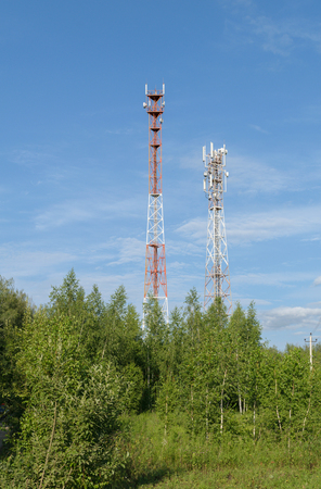 Two towers with a cellular mobile radio antennas are among the trees
