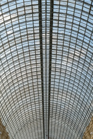 Transparent glass roof arch type, reinforced with a metal grate, over the huge room