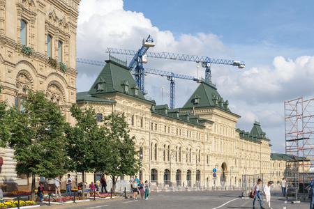 Moscow, Russia - July 07, 2016: People on Red Square near the facade of GUM building. Several tower cranes on background