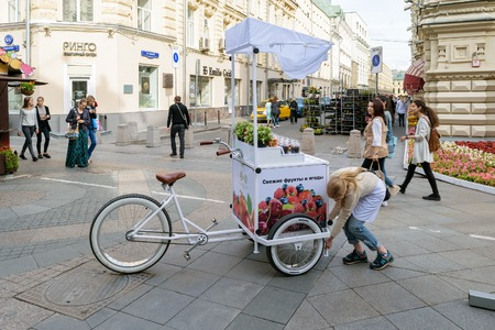 salespeople: Moscow, Russia - July 07, 2016: Girl sets the counter with a refrigerator, attached to the bike, for sale of fresh fruits and berries