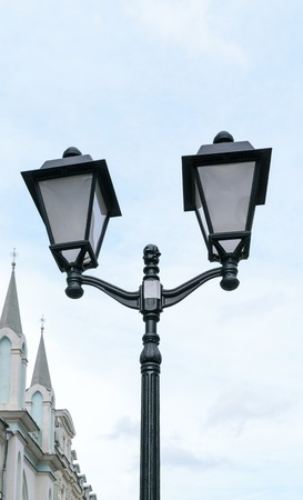 Black retro street lamp with two lights in the sky background. Stock Photo