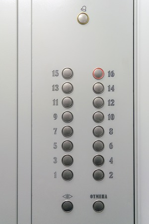 Metal elevator control panel with round buttons with numbers of floors.
