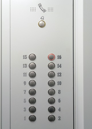 Elevator metal control panel with round buttons with numbers of floors.