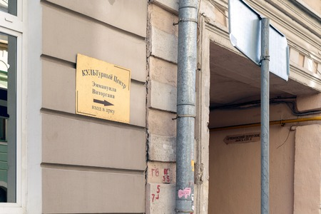 Moscow, Russia - July 14, 2016: Shiny metal plated tablet hanging on the wall, indicating the direction of the passage to the Cultural Centre Emmanuel Vitorgan (famous Russian actor) (address: Sechenovskiy Lane, Building 5, Building 2)