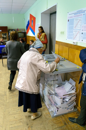 Orel, Russia - September 18, 2016: An older woman puts the ballot in the ballot box at polling stations on the day of elections to the State Duma