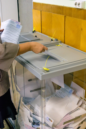 Orel, Russia - September 18, 2016: Woman puts the ballot in the ballot box at polling stations on the day of elections to the State Duma Editorial