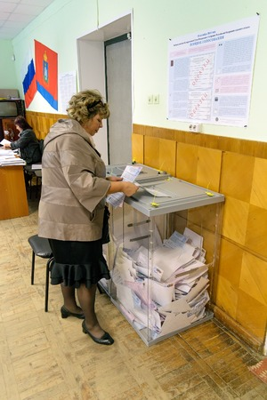 Orel, Russia - September 18, 2016: Woman puts the ballot in ballot box at polling stations on the day of elections to the State Duma