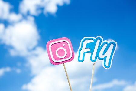KYIV, UKRAINE - MAY 25, 2019: paper cut Instagram icon and fly word on sticks on blue sky background