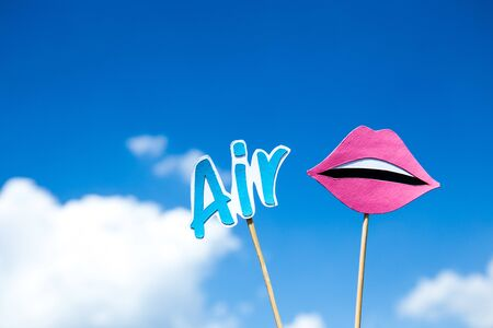 word air and paper cut mouth on sticks on blue sky background Banque d'images