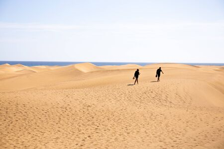 people walking on sand hills near Atlantic ocean against clear blue sky at sunny day in Maspalomas, Gran Canaria Stock Photo