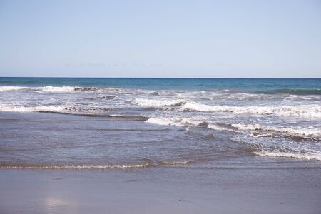 scenic view of Atlantic ocean with waves against clear blue sky at sunny day in Maspalomas, Gran Canaria