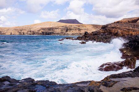 Atlantic ocean with waves and rocks against blue sky with clouds in Agaete, Las Palmas