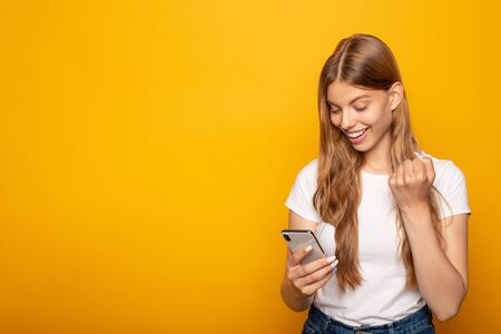 smiling girl using smartphone and showing yeah gesture isolated on yellow