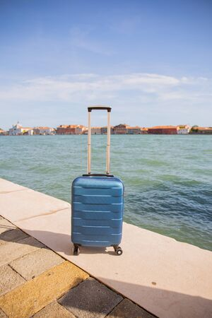 travel bag near water pond in dock at sunny day in Venice, Italy.