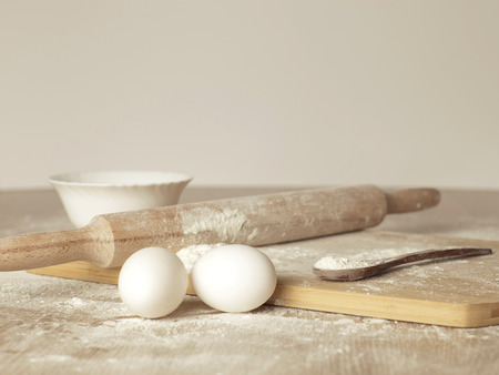 rollingpin: Preparations for homemade baking. Basic ingredients for baking. Kitchen utensil with eggs rolling-pin wood spoon meal. Meal on table with cutting board. Flour. baking Stock Photo
