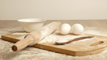 strew: Preparations for homemade baking. Basic ingredients for baking. Kitchen utensil with eggs rolling-pin wood spoon meal. Meal on table with cutting board. Flour. baking Stock Photo