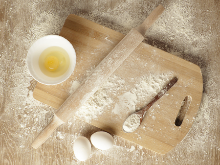 rollingpin: Preparations for homemade baking. Basic ingredients for baking. Kitchen utensil with eggs rolling-pin wood spoon meal. Meal on table with cutting board.