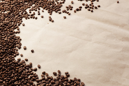 poke: Coffee beans on paper background. Paper texture coffee. Dark coffee roasted. Coffee beans