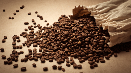 poke: Coffee beans on paper background. Paper texture coffee. Dark coffee roasted. Bag of coffee