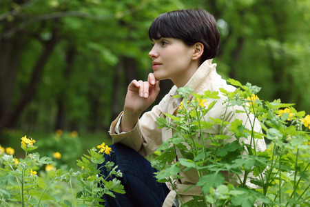 pacification: young and beautiful girl in the park among flowers Stock Photo