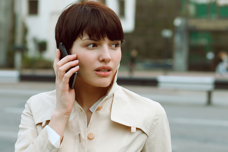 pensiveness: young and beautiful girl standing with phone in hand