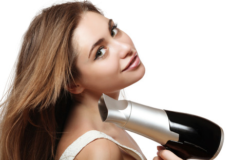 flaunt: young and beautiful brown-haired woman with long hair natural color and a hairdryer in the hands of Stock Photo