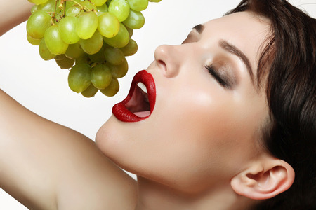 beautiful and sexy woman with bright makeup holding delicious grapes in hands photo