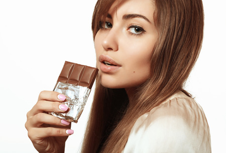 Beautiful and cute girl with green eyes is holding chocolate Фото со стока