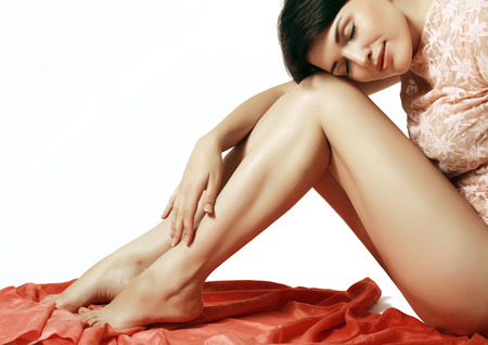 feet naked: young and beautiful girl hugging her silky smooth legs