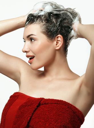 Pretty teenage girl in burgundy towel washes head Фото со стока