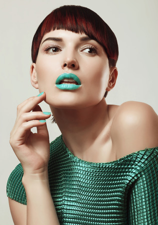 beautiful and sexy girl with bright makeup and hairstyle, manicure, turquoise lipstick